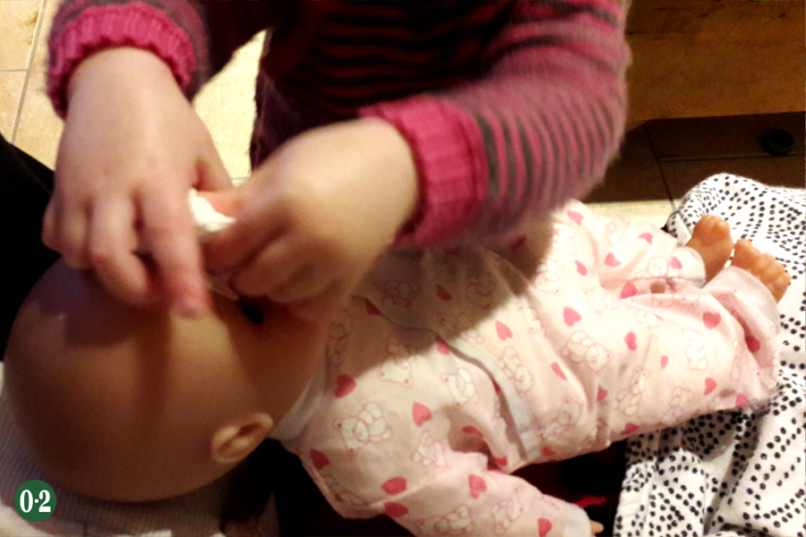 Kleinkind als fürsorgliche Puppenmutter